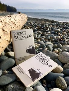 Pocket Worshop book resting against a log on a rocky beach